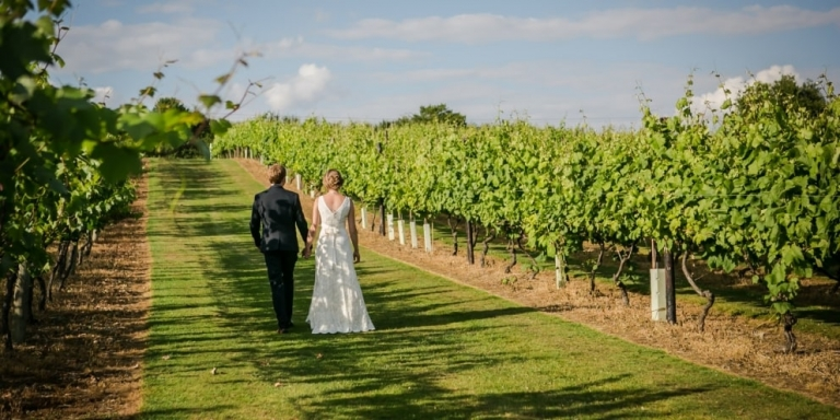 Couple-walking-through-field-after-wedding